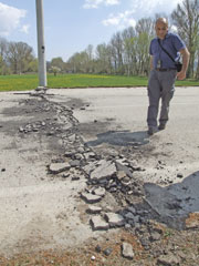 A geologist sureys the damage to a road